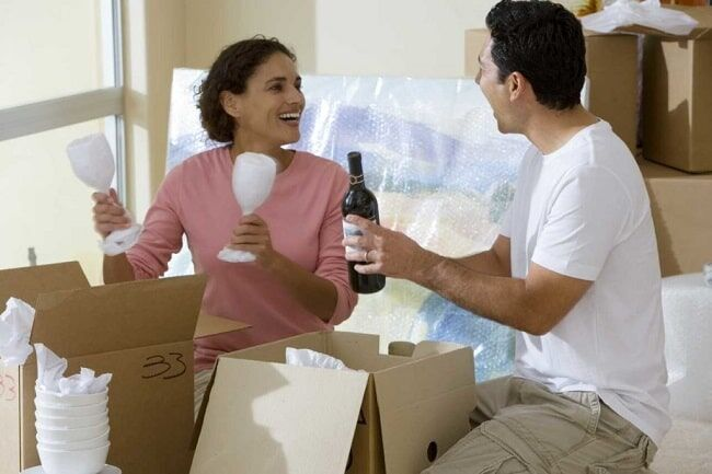 Young couple unpacking the boxes after moving in