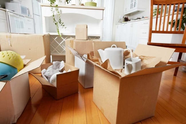 Carton boxes and interior items prepared for moving into new house near color wall